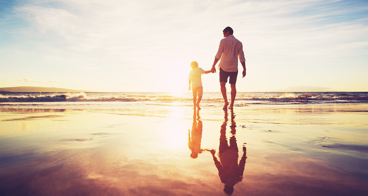 48345262 - father and son holding hands walking together on the beach at sunset